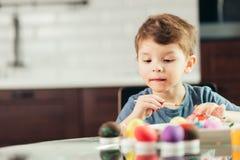Petit garçon heureux peignant des oeufs de pâques, des enfants et la créativité photos libres de droits
