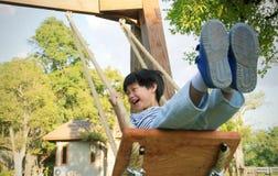 Petit garçon heureux riant et balançant sur une oscillation photos stock