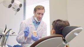 Petit garçon heureux souriant à la caméra pendant l'appointement médical avec le dentiste banque de vidéos
