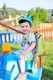 Petit garçon heureux sur un rond point Image libre de droits