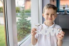 Petit garçon heureux tenant une inscription en bois avec le mot Photos stock