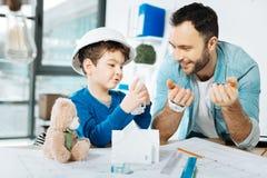 Petit garçon interrogeant son père au sujet du modèle de la maison 3D Images stock