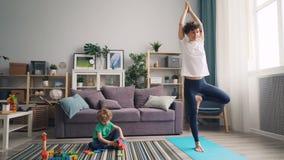 Petit garçon jouant avec des jouets sur le plancher quand sa mère sportive faisant le yoga sur le tapis banque de vidéos