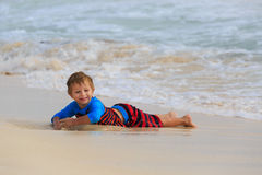 Petit garçon jouant avec des vagues sur la plage de sable Photos libres de droits