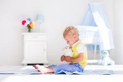 Petit garçon jouant avec l'animal familier de lapin Photos stock