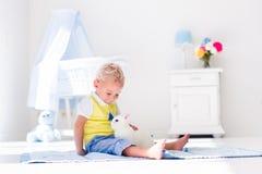 Petit garçon jouant avec l'animal familier de lapin Photo libre de droits