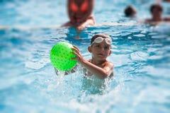 Petit garçon jouant avec la boule dans une piscine Photographie stock libre de droits