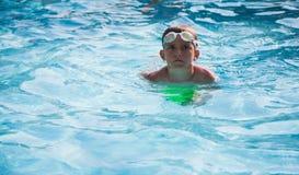 Petit garçon jouant avec la boule dans une piscine Image stock