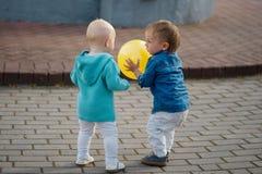 Petit garçon jouant avec la boule jaune Photo libre de droits