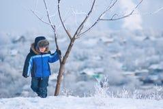 Petit garçon jouant avec la neige Photographie stock