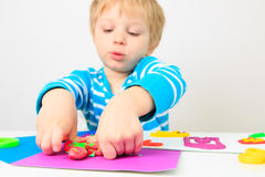Petit garçon jouant avec la pâte, l'éducation et la garde d'argile images stock