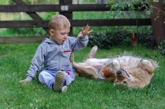 Petit garçon jouant avec le chien Photographie stock libre de droits