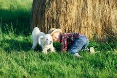 Petit garçon jouant avec le chien près de la meule de foin en nature Image libre de droits