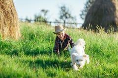 Petit garçon jouant avec le chien près de la meule de foin en nature Image stock