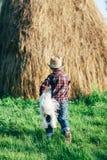 Petit garçon jouant avec le chien près de la meule de foin en nature Photo stock