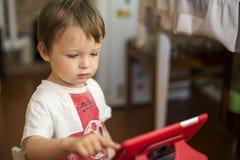 Petit garçon jouant avec le comprimé numérique enfant à l'aide d'un comprimé numérique photos libres de droits
