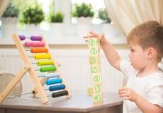 Petit garçon jouant avec le jouet d'abaque à l'intérieur Photos stock