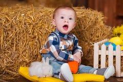 Petit garçon jouant avec le lapin blanc d'intérieur Amusement de Pâques de ressort pour des enfants concept d'enfance heureux Image stock