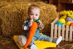 Petit garçon jouant avec le lapin blanc et la carotte d'intérieur Amusement de Pâques de ressort pour des enfants concept d'enfan Photographie stock
