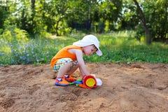 Petit garçon jouant avec le sable sur le terrain de jeu Photographie stock libre de droits