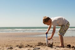 Petit garçon jouant avec le seau et le sable sur la plage Images libres de droits