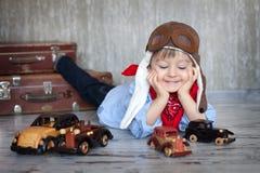 Petit garçon, jouant avec les voitures en bois images stock