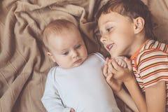 Petit garçon jouant avec nouveau-né sur le lit Photos libres de droits