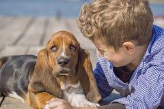 Petit garçon jouant avec son chien par la rivière Photographie stock libre de droits