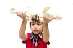 Petit garçon jouant avec un avion de jouet sur le backgr blanc Image libre de droits