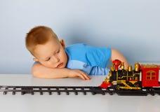 Petit garçon jouant avec une locomotive de jouet Image stock
