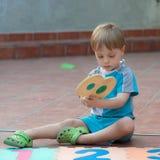 Petit garçon jouant dans l'arrière-cour Photographie stock libre de droits