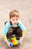 Petit garçon jouant dans le véhicule de jouet Photographie stock