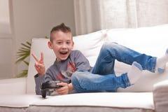 Petit garçon jouant des jeux vidéo Images stock