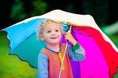 Petit garçon jouant en parc pluvieux d'été Photos libres de droits