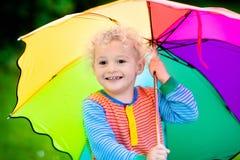 Petit garçon jouant en parc pluvieux d'été Photographie stock libre de droits