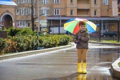 Petit garçon jouant en parc pluvieux d'été Enfant avec le rai coloré Image stock