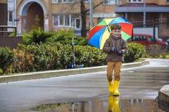 Petit garçon jouant en parc pluvieux d'été Enfant avec le rai coloré Photo libre de droits