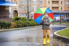 Petit garçon jouant en parc pluvieux d'été Enfant avec le rai coloré Photographie stock libre de droits