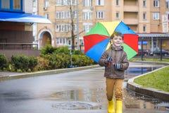 Petit garçon jouant en parc pluvieux d'été Enfant avec le rai coloré Photo stock