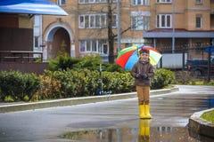 Petit garçon jouant en parc pluvieux d'été Enfant avec le rai coloré Photos stock