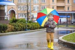 Petit garçon jouant en parc pluvieux d'été Enfant avec le rai coloré Photographie stock