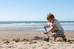 Petit garçon jouant en sable sur la plage Images libres de droits