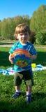 Petit garçon jouant la boule sur l'herbe Photos libres de droits