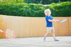 Petit garçon jouant le badminton sur le terrain de jeu Image libre de droits