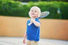 Petit garçon jouant le badminton sur le terrain de jeu Images stock