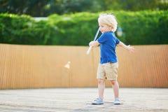 Petit garçon jouant le badminton sur le terrain de jeu Photo libre de droits