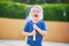 Petit garçon jouant le badminton sur le terrain de jeu Photo stock