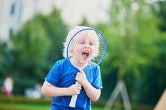 Petit garçon jouant le badminton sur le terrain de jeu Photographie stock