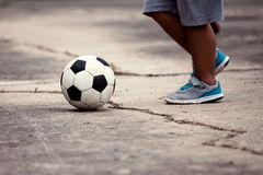 Petit garçon jouant le football dans la campagne Images stock