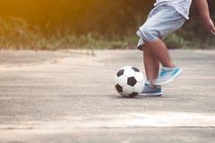 Petit garçon jouant le football dans la campagne Photo libre de droits